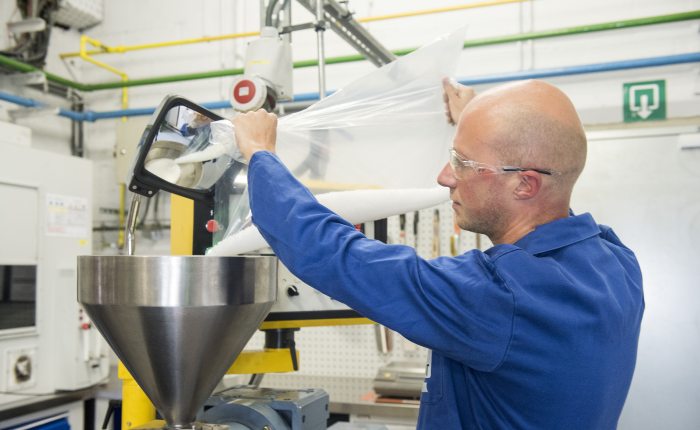 plant worker pouring a substance into equipment at our Pepinster, Belgium facility